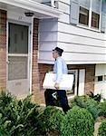 1960s DELIVERY MAN UNIFORM FRONT DOOR SUBURBAN HOUSE DELIVERING LARGE PARCEL SERVICE WORKER