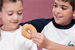 Gros plan d'un garçon de nourrir un beignet à sa sœur