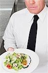 Waiter holding vegetable salad in plate