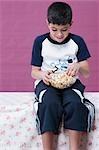 Gros plan d'un garçon de manger un bol de pop-corn
