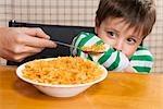 Close-up of a boy refusing corn flakes