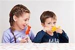 Garçon et sa sœur tenant des bonbons