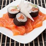 Gros plan de sushi roule sur des tranches de saumons