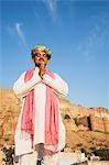 Homme en position de prière avec fort dans le fond, le Fort de Meherangarh, Jodhpur, Rajasthan, Inde
