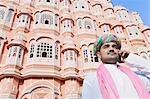 Homme de parler sur un téléphone mobile devant un palace, Hawa Mahal, Jaipur, Rajasthan, Inde