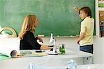 Garçon résoudre des problème de mathématiques sur le tableau noir, en regardant des enseignants pour une aide