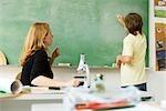 Garçon regardant l'enseignant par écrit sur le tableau noir