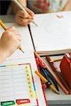 Enfants écrivant dans des cahiers, des fournitures scolaires à proximité, recadrée