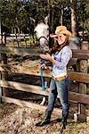 Portrait de jeune cowgirl avec blanc cheval hongre sur la ferme