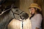 Portrait de jeune cowgirl avec blanc cheval hongre dans l'écurie