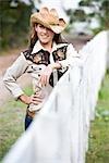 Portrait de jeune cow-girl à la clôture de ferme