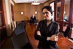 Portrait of smiling businesswoman in boardroom, man in background