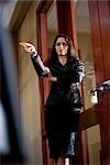 Portrait of mid adult businesswoman standing in boardroom gesturing