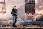 Junger Mann stand auf dem gepflasterten Gehweg durch alte Hauswand
