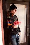 Junger Mann, der Blumen in Tür
