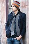 Junger Mann in warme Kleidung Schiefe Wand des Gebäudes