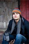 Porträt des jungen Mannes tragen warmen Kleidung, die draußen sitzen hautnah