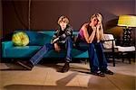 Bored young teenage couple sitting on sofa indoors