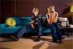 Young teenage couple sitting on sofa indoors
