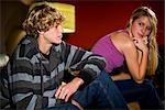 Teenagers sitting on sofa indoors