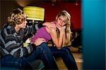 Thoughtful young teenage couple sitting on sofa indoors