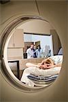 Patient couché sur machine CT-scan, tandis que les médecins consulter à fond