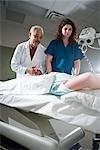 Healthcare workers preparing patient for CAT scan