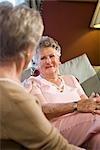 Elderly woman sitting on sofa chatting with friend