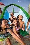 Enfants multiethniques sur toboggan au parc aquatique