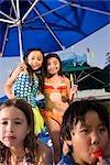 Multiethniques enfants au parc aquatique en été manger des sucettes glacées