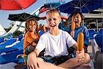 Garçons multiethniques au parc aquatique en été manger des saucisses sur bâtonnet
