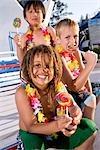 Garçons avec les sucettes et les leis de fleurs au parc de l'eau en été
