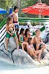 Groupe multiethnique des enfants au parc aquatique en été