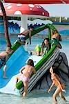 Multi-ethnic children on slide at water park in summer