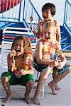 Garçons avec les sucettes et les leis de fleurs sur la terrasse de la piscine en été