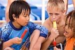 Garçons multiethniques manger des sucettes glacées au parc aquatique