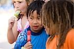 Multiethniques enfants manger des sucettes glacées au parc aquatique