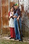 Debout de couple senior à l'extérieur de la grange altérée