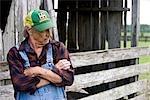 Senior homme debout près de grange avec une expression sérieuse sur le visage