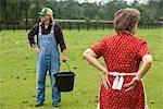 Senior couple travaillant sur la position ferme dans les verts pâturages