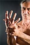 Old man with arthritis pain in hand, studio shot
