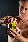 Senior man with arthritis opening pickle jar, studio shot