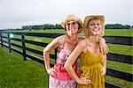 Mère et fille adolescente en robes debout près de la clôture de ferme