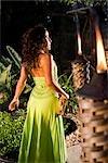 Young Hispanic woman in green dress holding tambourine on tropical island