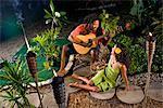 Young Jamaican man serenading beautiful woman in tropical garden