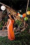 Young Hispanic woman in orange dress standing in tropical garden on island