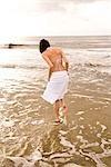 Rear view of young woman in skirt and bikini top walking in ocean on beach