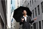 homme d'affaires tenir parapluie, regardant vers le haut dans le ciel