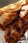 Close-up of wavy redhead woman in silk shirt