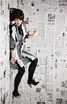 Jeune femme tomber un mur recouvert de journaux, studio shot